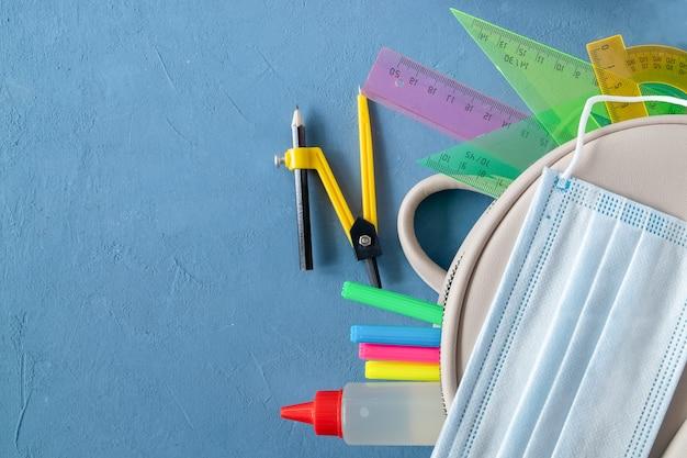 Artykuły szkolne, plecak i maska medyczna na niebieskim tle