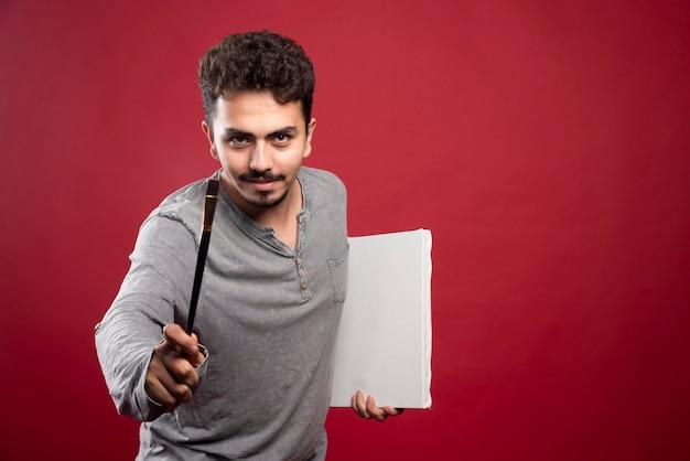Artysta Bardzo Uważnie Patrzy Na Swojego Klienta, Aby Namalował Szczegółowy Portret. Darmowe Zdjęcia