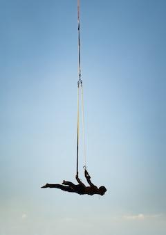 Artysta cyrkowy na pasach anteny na tle błękitnego nieba