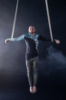 Artysta cyrkowy na pasach powietrznych z kostiumem