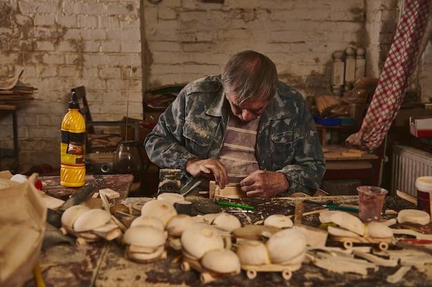Artysta drewna, rzemieślnik, stolarz w warsztacie do produkcji ręcznie robionych zabawek drewnianych. bezpieczne zabawki ekologiczne dla dzieci