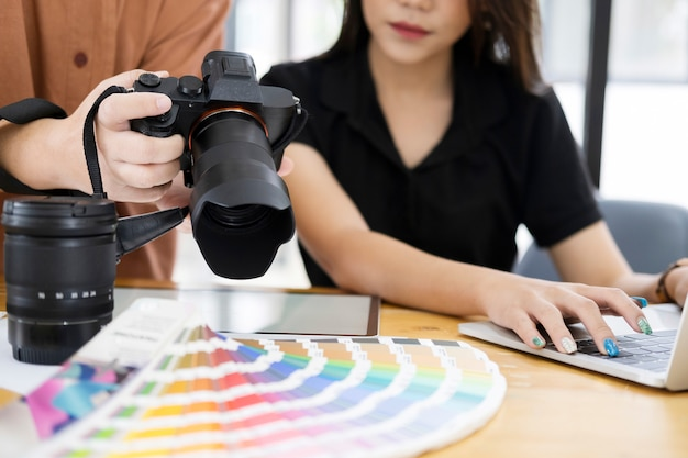 Artysta fotograf i projektant graficzny, wybierając zdjęcia z aparatu.