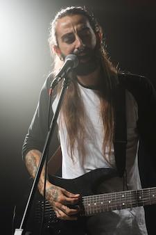Artysta gra na gitarze i śpiewa
