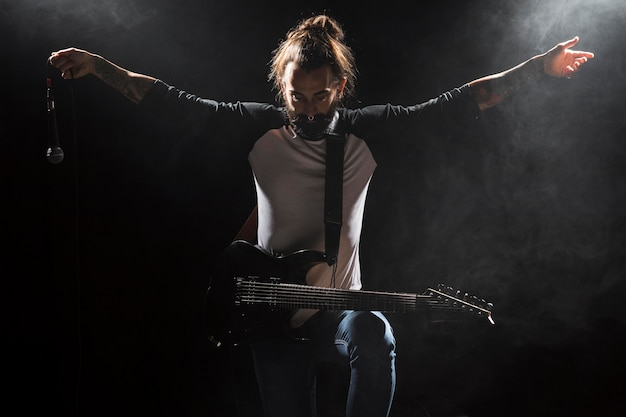 Artysta gra na gitarze i trzyma mikrofon