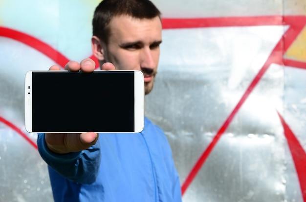 Artysta graffiti pokazuje smartfon z pustym