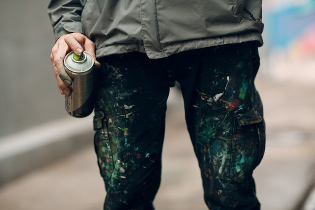 Artysta graffiti w ubraniach poplamionych farbą w sprayu może w dłoni