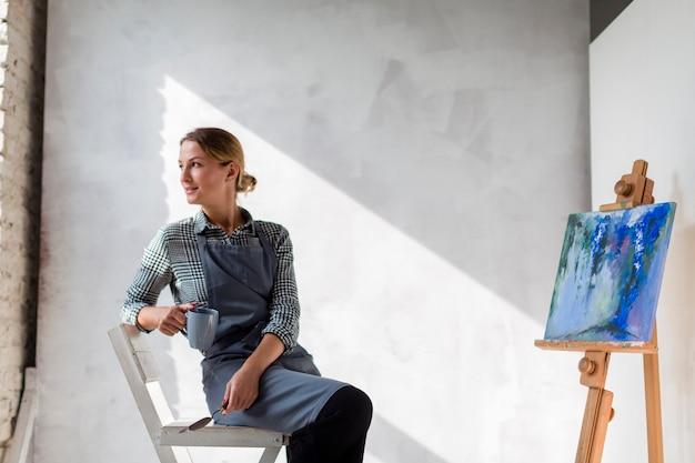 Artysta kobieta pozuje na krześle z kanwą