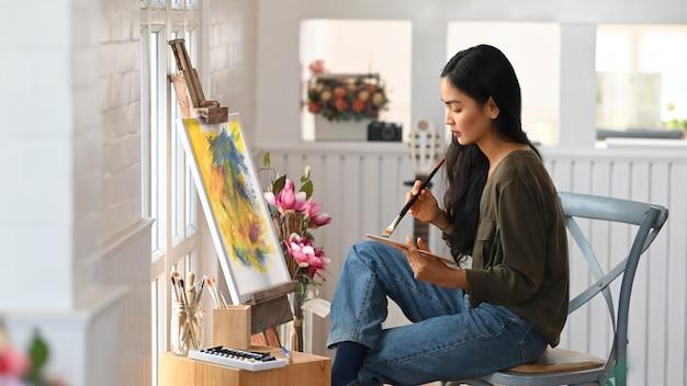 Artysta kobieta siedzi i rysunek kolor wody w studio sztuki.