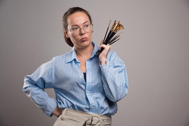 Artysta kobieta trzyma pędzle malarskie na szaro. zdjęcie wysokiej jakości