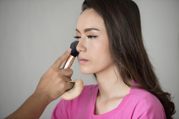 Artysta makijażu w pracy. makijaż azja kobieta modelka
