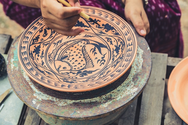 Artysta malujący wzór ryb w ceramice rzemieślniczej