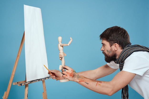 Artysta maluje obraz na płótnie za pomocą sztalugi