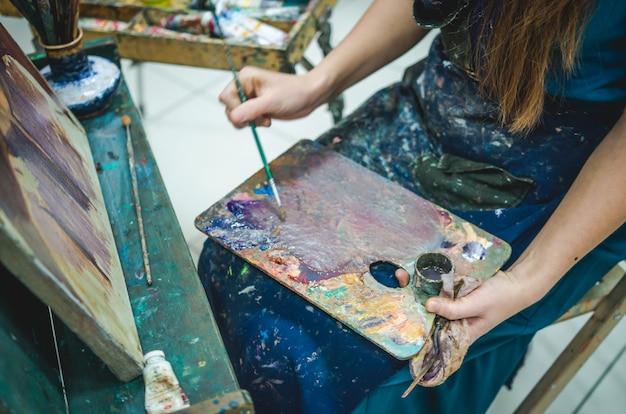 Artysta maluje obraz w studio. zamknąć widok