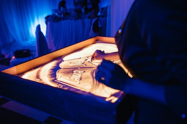 Artysta maluje obrazy fabularne piaskiem na oświetlonym stole
