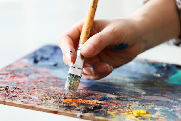 Artysta maluje pędzlem olejnym