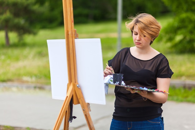 Artysta młoda kobieta maluje na płótnie miejski krajobraz