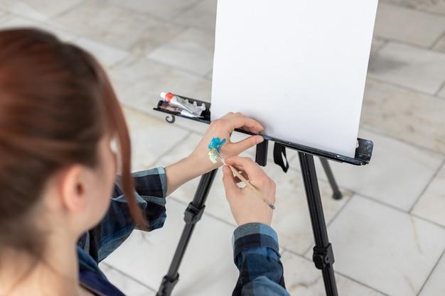 Artysta młoda nastolatka miesza farby olejne na dłoni. białe płótno z miejscem do kopiowania znajduje się na czarnej sztaludze.