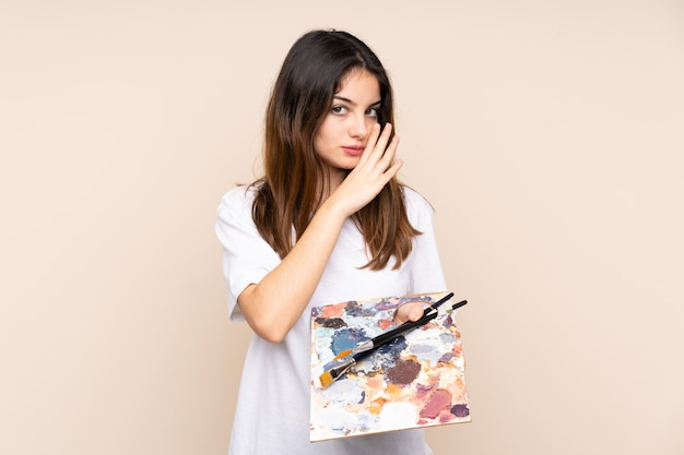 Artysta młody człowiek trzyma paletę na beżowej ścianie szepcząc coś