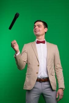Artysta. młody elegancki mężczyzna rozmawia trzymając mikrofon, na białym tle w studio.