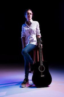 Artysta na scenie siedzi na krześle i trzyma gitarę
