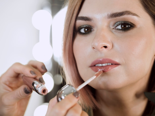 Artysta nakładający błyszczyk na model