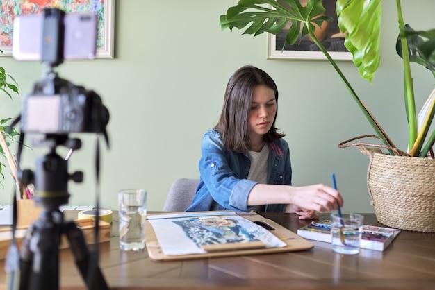 Artysta, nastolatka, rysuje i nagrywa kamerą wideo na swoim blogu. farby, rysunki na domowym stole, aparat na statywie, rysunek opowiadającej blogerce blogerce. koncepcja technologii, sztuki, młodzieży, edukacji