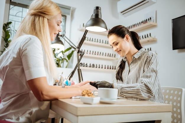 Artysta paznokci. przyjemna, ciemnowłosa stylistka paznokci dobrze czuje się podczas pracy rozmawiając ze swoim stałym klientem