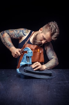 Artysta pracujący ze skórą przy pracy nad swoim nowym skórzanym produktem