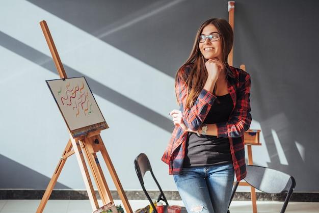 Artysta pretty pretty girl maluje na płótnie na sztaludze.