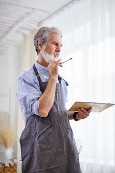 Artysta rysuje na płótnie sztalugowym, starszy siwy mężczyzna w fartuchu cieszy się procesem malowania, w jasnym pokoju.