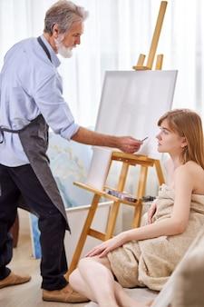 Artysta rysunek portret modelki na płótnie, młoda dama kaukaski siedzi na kanapie pozuje do sztuki