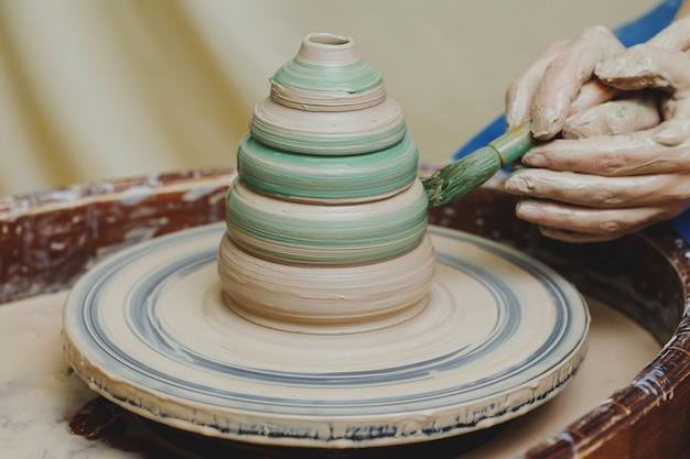 Artysta rzemieślnik malowanie garnka z pędzlem