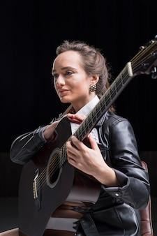 Artysta siedzi bokiem przytulając gitarę w studio
