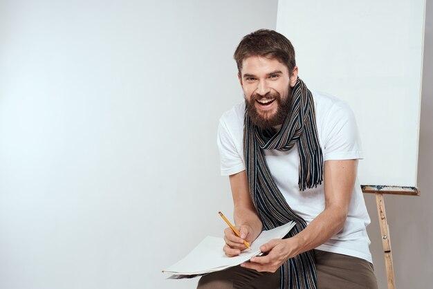 Artysta siedzi na krześle, rysunek w pobliżu sztalugi