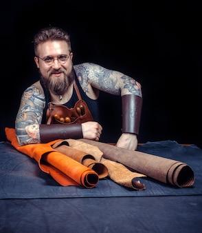 Artysta skórzany pracujący jako rzemieślnik w sklepie / rzemieślnik skórzany przetwarza obrabiany przedmiot ze skóry na półce.