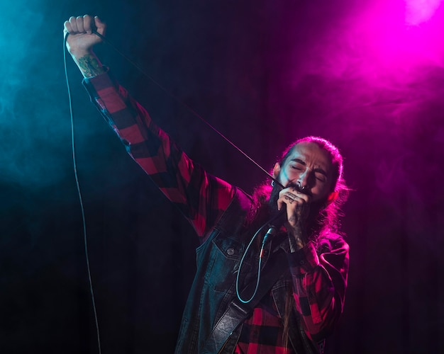 Artysta śpiewa i trzyma kabel mikrofonowy