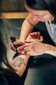 Artysta stosując tatuaż henną mehndi na ręka