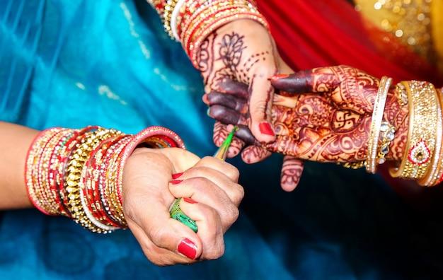 Artysta stosujący tatuaż henną na rękach kobiet. mehndi to tradycyjna indyjska sztuka dekoracyjna. zbliżenie