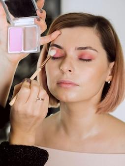 Artysta stosuje różowy cień do powiek na kobiecie