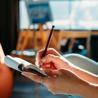 Artysta szkicujący. obszar roboczy studio. kobieta malarz robi szkic ołówkiem w podkładce.