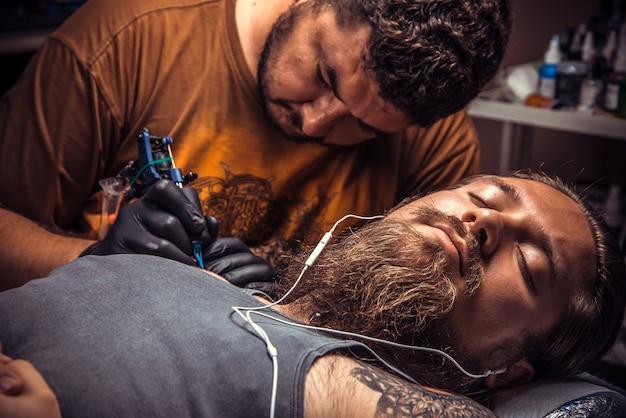 Artysta tatuażu pokazujący proces wykonywania tatuażu w salonie tatuażu