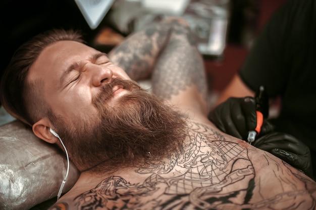 Artysta tatuażu przedstawia proces tatuowania studia tatuażu.