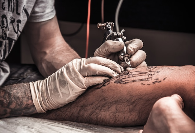 Artysta tatuażu w trakcie wykonywania tatuażu