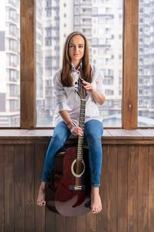 Artysta trzyma gitarę w pomieszczeniu