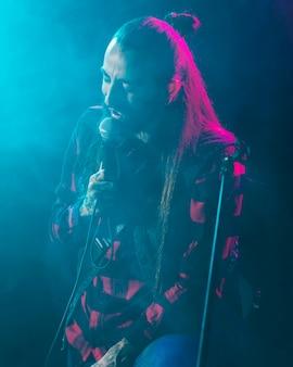 Artysta trzyma mikrofon na scenie i śpiewa