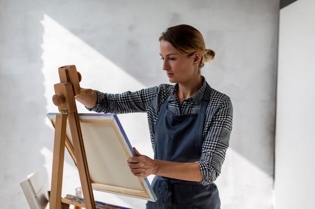 Artysta trzyma płótno w studio