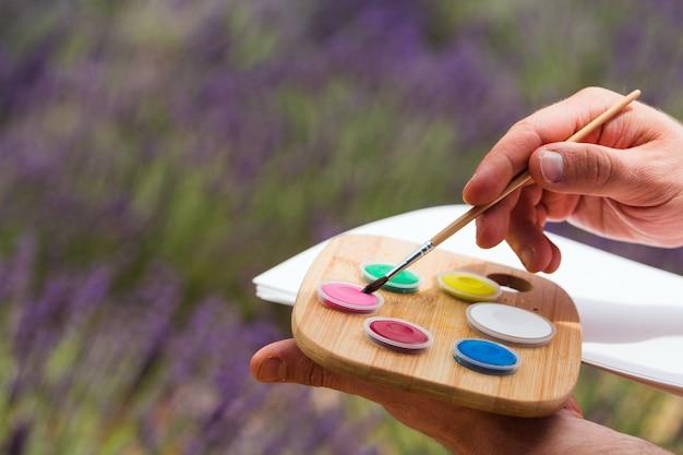 Artysta trzyma w dłoniach paletę z farbami i zawijany rysunek na kartce papieru