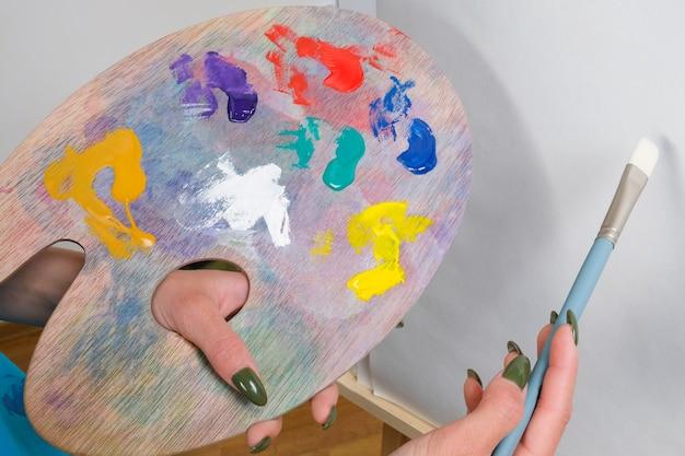 Artysta trzyma w rękach paletę i pędzel