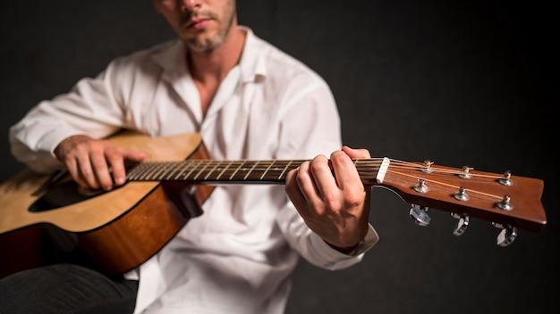 Artysta w białej koszuli gra na gitarze akustycznej w studio