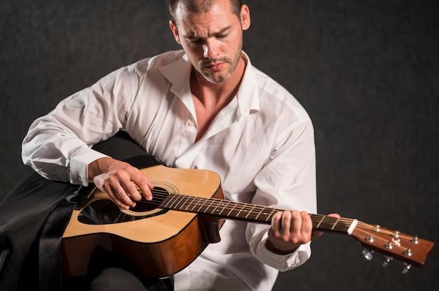 Artysta w białej koszuli siedzi i gra na gitarze